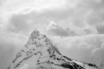 Fototapete - High snowy mountains in fog and cloudy sky at winter