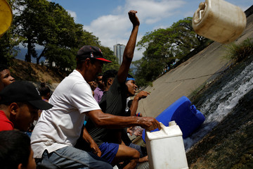 People use plastic containers to collect water released through a sewage drain that feeds into the Guaire River in Caracas