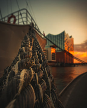 brown rope hanging by metal barrier from ship during golden hour