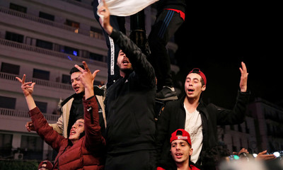 People celebrate on the streets after President Abdelaziz Bouteflika announced he will not run for a fifth term, in Algiers