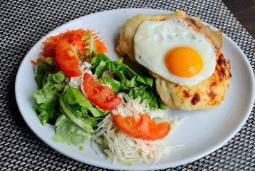 French 'croque madame' sandwich made of baked ham and cheese and topped with a fried egg, served with a salad