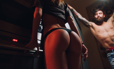 Sexy couple in the kitchen at night.Bearded guy with tattoos and sexy girl