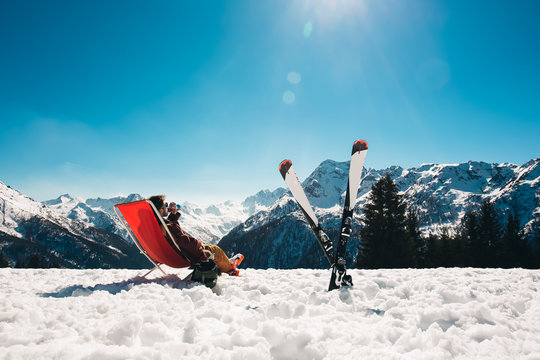 guy chilling out on the slope after skiing in Aprica ski resort with his skies next to him