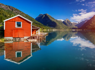 Photo sur Aluminium Pôle Beautiful fishing house on fjord. Beautiful nature with blue sky, reflection in water and fishing house. Norway