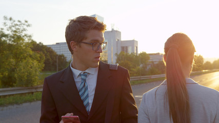 CLOSE UP: Handsome guy looking at his smartphone sees a gorgeous businesswoman.