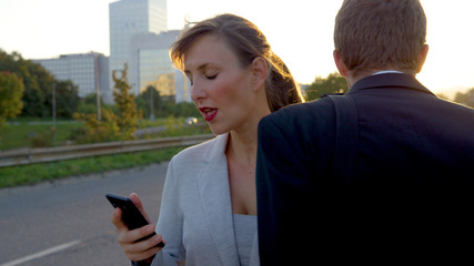 CLOSE UP: Beautiful businesswoman looking at her smartphone crashes into yuppie.