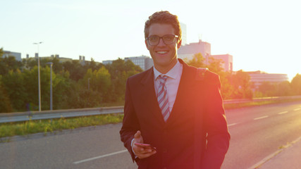 PORTRAIT: Smiling yuppie walking down the sunny sidewalk with cell phone in hand