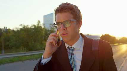 CLOSE UP: Young businessman gets bad news over the phone while walking home.