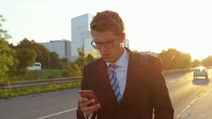 LENS FLARE: Worried yuppie reading a long text message on his way home from work