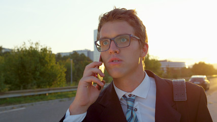 CLOSE UP: Young manager gets bad news over phone while walking through the city.