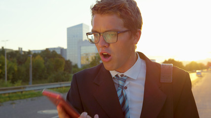 CLOSE UP: Stressed young manager shouts at his smartphone while walking to work.