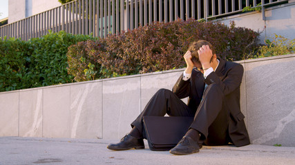 Sad young man sits on the concrete sidewalk and buries his head in his hands.
