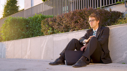 SUN FLARE: Businessman sits on the pavement and shakes his head after losing job