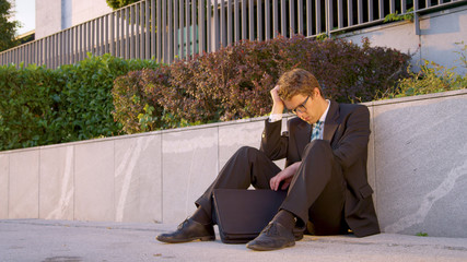 Young Caucasian businessman sits on the side of the road after losing his job