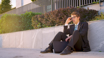 LENS FLARE: Businessman sitting on the street and shaking his head in disbelief.