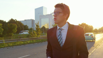 LENS FLARE: Anxious businessman looking around the city after getting bad news.