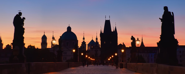 Fotomurales - Prague at night, panoramic image. Charles Bridge early in the morning with unrecognizable tourists and photographers