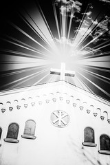 Black and white photo or photography of sunrays coming from the Christianity cross on top of a church