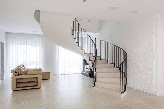 spiral staircase in bright interior with white brick wall in elite expensive apartment