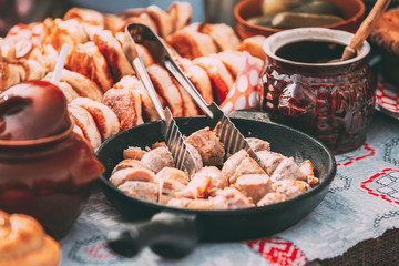 Dishes of the traditional Belarusian cuisine - fried bacon and meat sausages, pastries.
