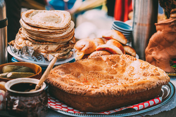 Dishes of the traditional Belarusian cuisine - pie, pancakes and honey.
