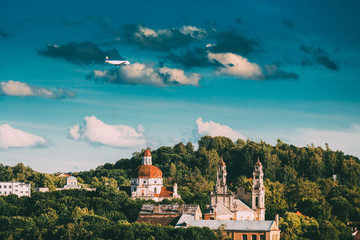 Vilnius, Lithuania. Plane Flying Over Church Of The Ascension And Church Of The Sacred Heart Of Jesus Among Green Foliage