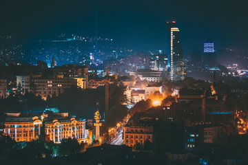 Tbilisi, Georgia. Construction Development Of Modern Architecture On Background Of Urban Night Cityscape. Evening Night Scenic Aerial View Of City Center
