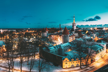 Tallinn, Estonia. Panorama Of Traditional Medieval Houses, Old Narrow Streets And Ancient Towers With Fortification Walls In Evening, Night Illumination. Blue Sky Background With Copyspace