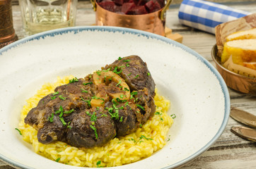 Beef osso bucco with risotto on rustic background.