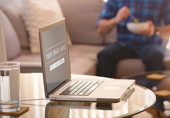 User on Laptop on Kitchen Table Mockup