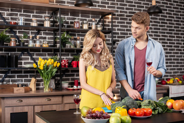 Blonde-haired wife cutting pepper for salad standing near her man