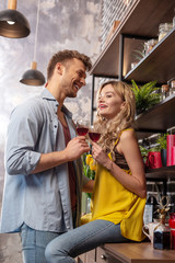 Loving bearded man feeling cheerful drinking wine with his girlfriend