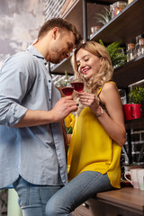 Cute couple clanging glasses with red wine spending time at home