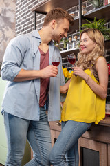 Young loving couple wearing jeans drinking red wine in the kitchen