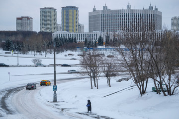 Moscow, Russia - March, 4, 2019: image of cars driving on the highway in winter against the background of residential buildings in Moscow