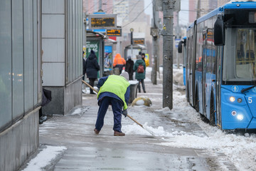 Moscow, Russia - March, 4, 2019: image of snow clearing by people from public utilities in Moscow near the bus stop