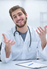 Handsome medical doctor in white coat is offering his hand