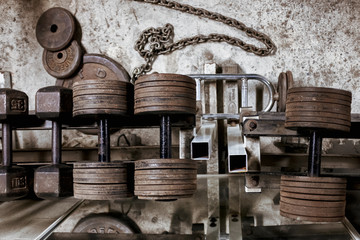 Rusted dumbbells and weights on a on a rack in a hardcore ,bodybuilders , weight room. Wall mural
