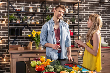 Couple feeling excited while cooking dinner together and drinking wine