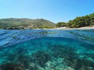 Spain Costa Brava coastline with fish and seagrass underwater, Mediterranean sea, Cala Montjoi, Roses, Catalonia, split view half over and under water