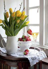 Tulips on a table in a living room. Champagne with strawberries.
