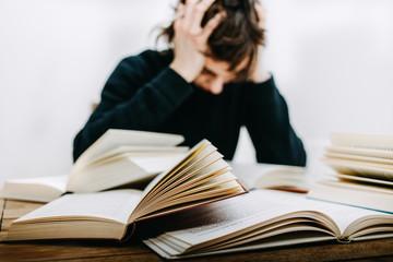 Student sitzt verzweifelt am Schreibtisch vor im einige aufgeschlagene Bücher