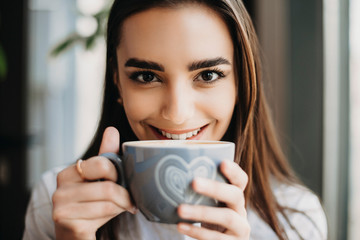 Close up portrait of an amazing caucasian girl looking at camera smiling while holding near her lips a cup of hot coffee in a coffee shop .