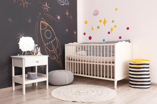 Stylish baby room interior with comfortable bed