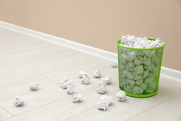 Metal bin and crumpled paper on floor near color wall, space for text