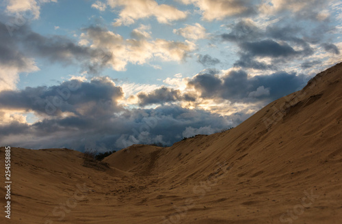 volumetric clouds on a background of sandy desert at sunset