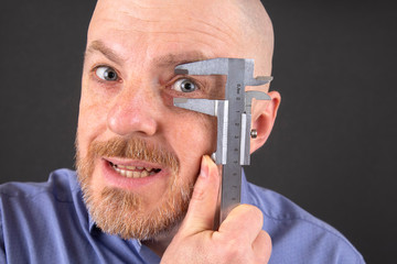 man measures the size of his eye measuring device caliper