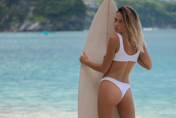 magnificent view of back of slim girl in bikini with surf board in sunny day