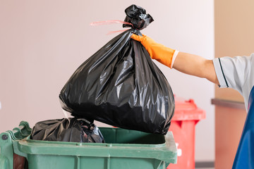 A woman worker holding black garbage bag into recycle bin.Maid and infection waste bin at the indoor public building.Red bin with waste bag on floor in the hospital.Infectious control.