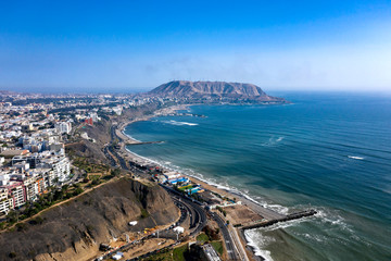 "Aerial view of Lima's shoreline including the districts of Barranco and Chorrillos, with ""Morro Solar"" on the background. Clear and bright day, travel and destinations concept."
